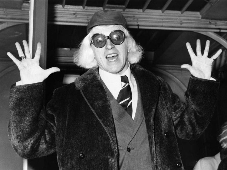 British disc jockey, broadcaster and charity worker Jimmy Savile arriving in London, on his way to Buckingham Palace where he is to be awarded an OBE