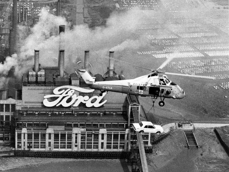 In a 1970 publicity exercise, Ford's one millionth export Cortina car is airlifted by a Westland Wessex helicopter over Ford's Dagenham plant on its way to Belgium, where its new owner is waiting with the keys