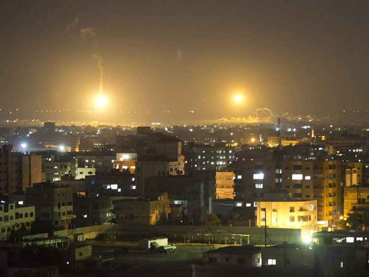 Artillery flares illuminate the sky following an Israeli air strike in Gaza City.