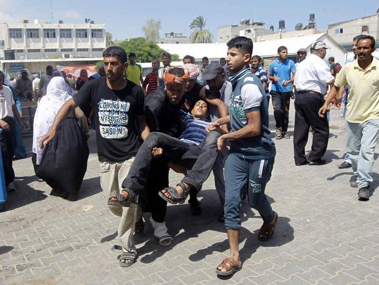 Palestinians carry an injured man following an Israeli military strike on a UN school.