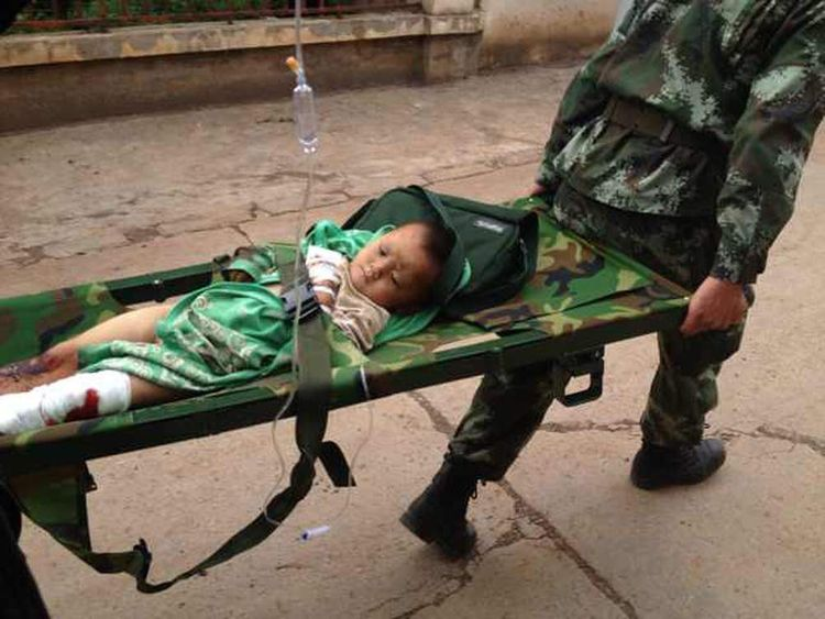 An injured child is carried on a stretcher after the quake in Yunnan province.