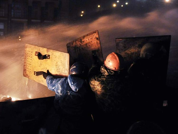 Protesters protect themselves with shields from police water cannon at the barricades at Independence square in Kiev.