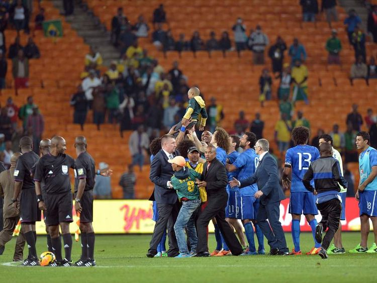Security prevent a young South African supporter from approaching Brazilian players, as a younger fan is held aloft.