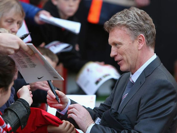 David Moyes signs autographs for fans ahead of Manchester United's match against Aston Villa at Old Trafford.