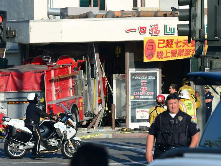 A motorcycle policeman arrives on the scene in Monterey Park, California, where two fire engines chasing a fire crashed into each other.