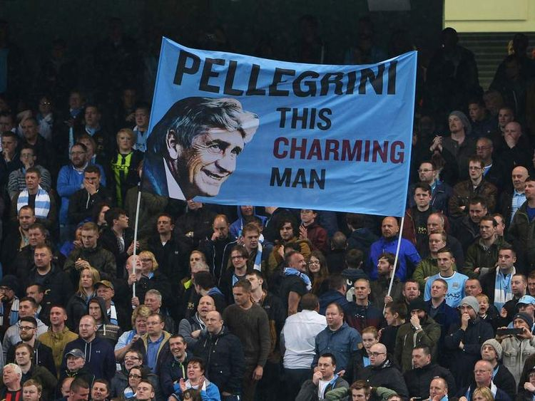 Manchester City fans hold a banner about their team's manager Manuel Pellegrini.