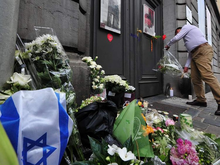 A man lays flowers as he pays his respects in front of a makeshift memorial at the entrance of the Jewish Museum in Brussels.