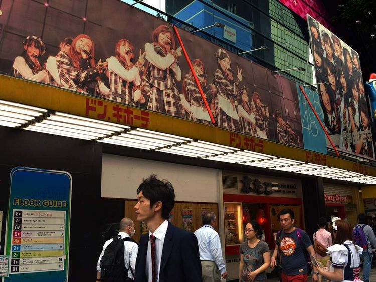 Pedestrians pass before the AKB48 theatre in Tokyo on May 26, 2014.