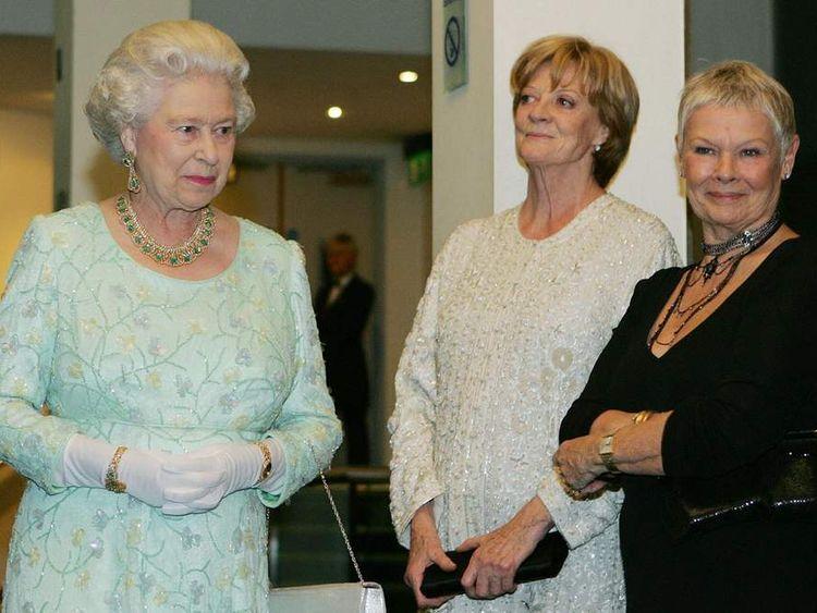 Queen Elizabeth II (L) walks past Dame M