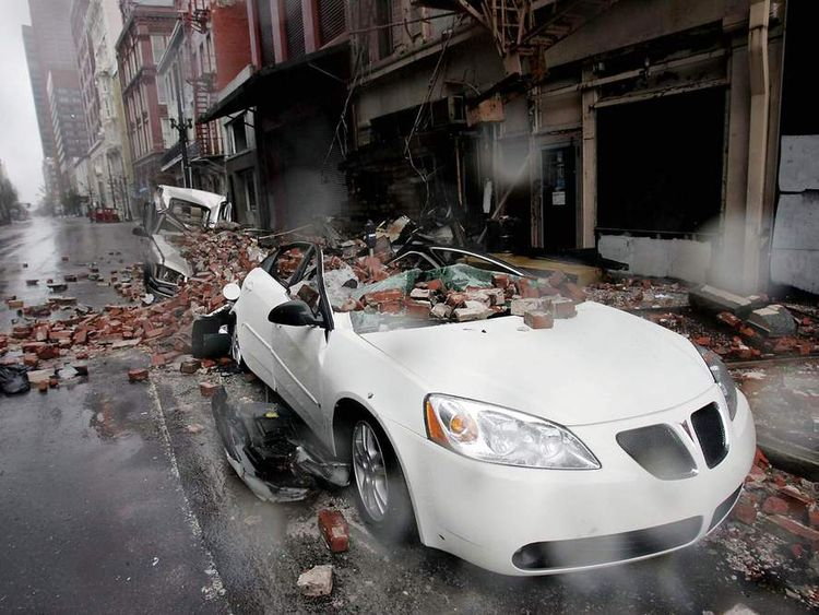 Cars sit along a side street damaged by falling debris in the French quarter of New Orleans
