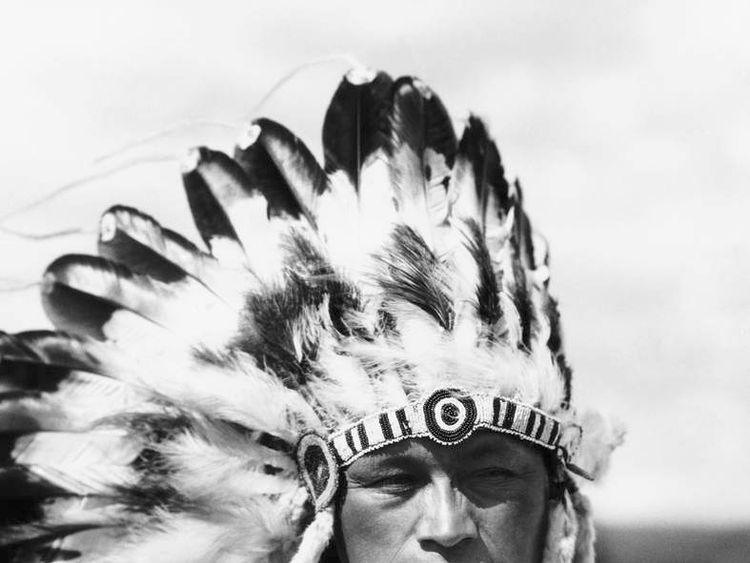 A Sioux Native American man wearing a large headdress