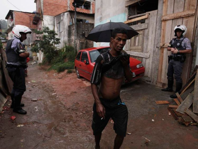 A man walks past Police officers in the Brasilandia favela during a security operation