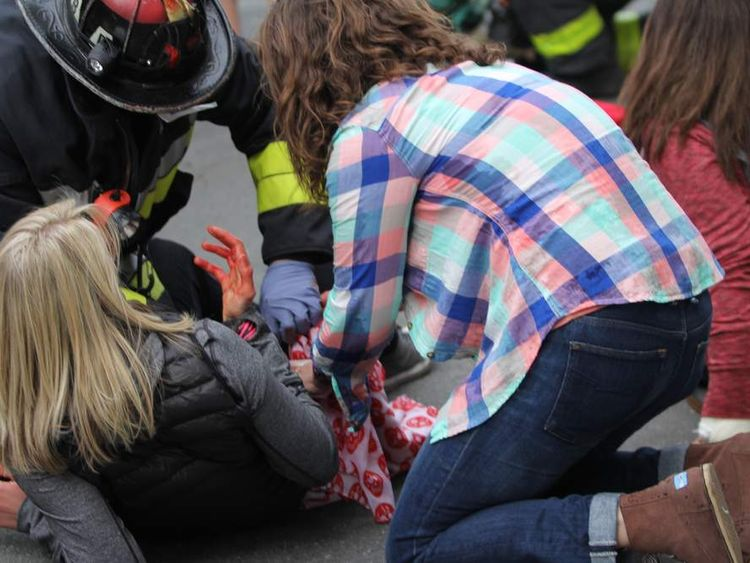 A first responder and a firefighter attend to an injured woman after a two bomb blasts at the finish of the Boston marathon. Photo courtesy of Kenshin Okubo/Daily Free Press Staff