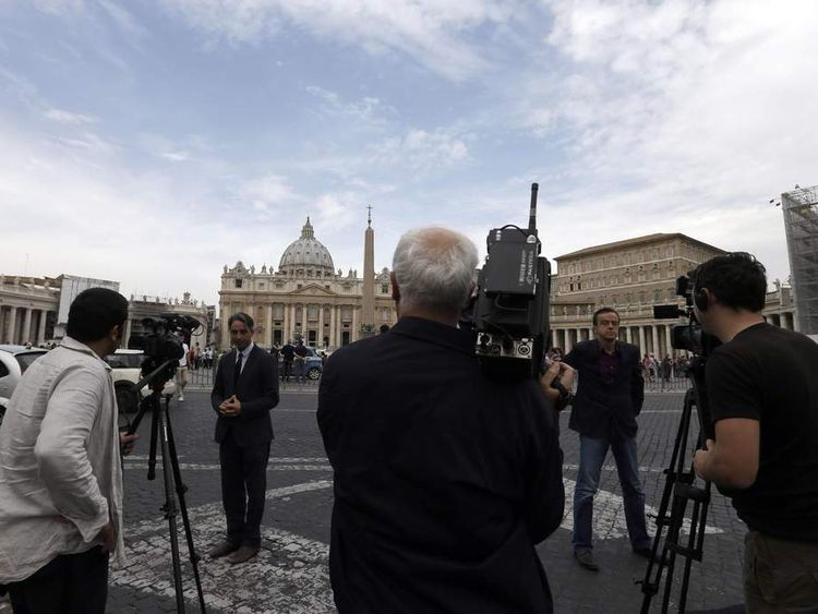 TV journalists stand up in front of the Vatican, Saturday Sept. 29, 2012. The Vatican opened the public trial Saturday of the pope's butler for allegedly stealing and leaking papal correspondence to a journalist,
