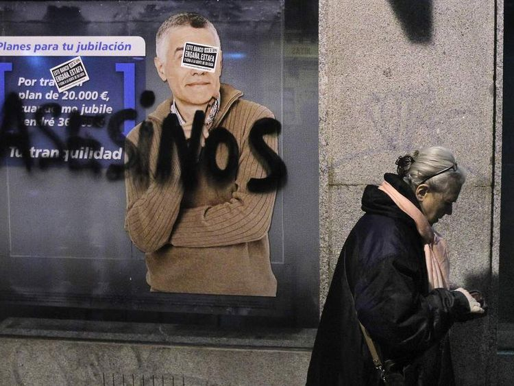 A woman looks in her wallet as she passes a bank painted with graffiti reading: 'Assassin'