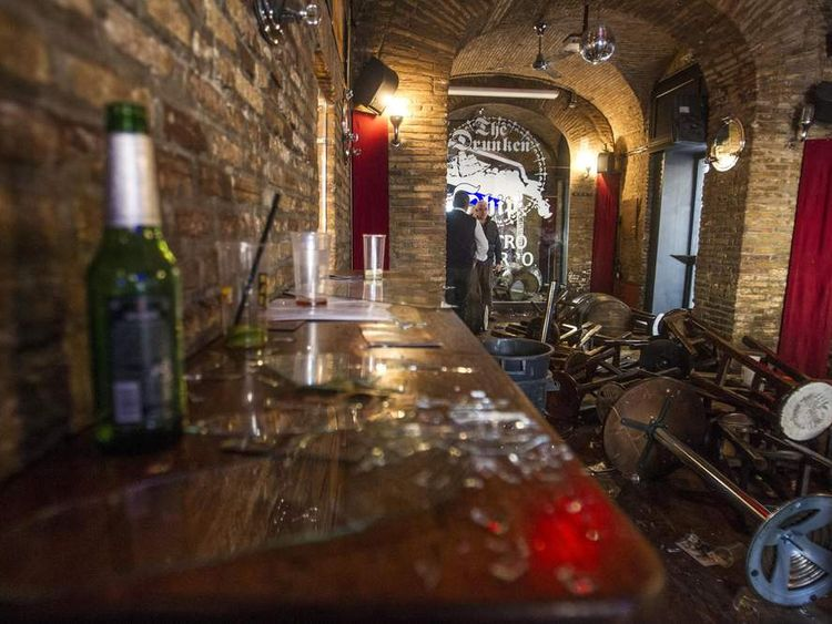 "Broken glass, and overturned tables and stools are seen inside ""The Drunken Ship"" pub in Rome's central Campo dei Fiori square"