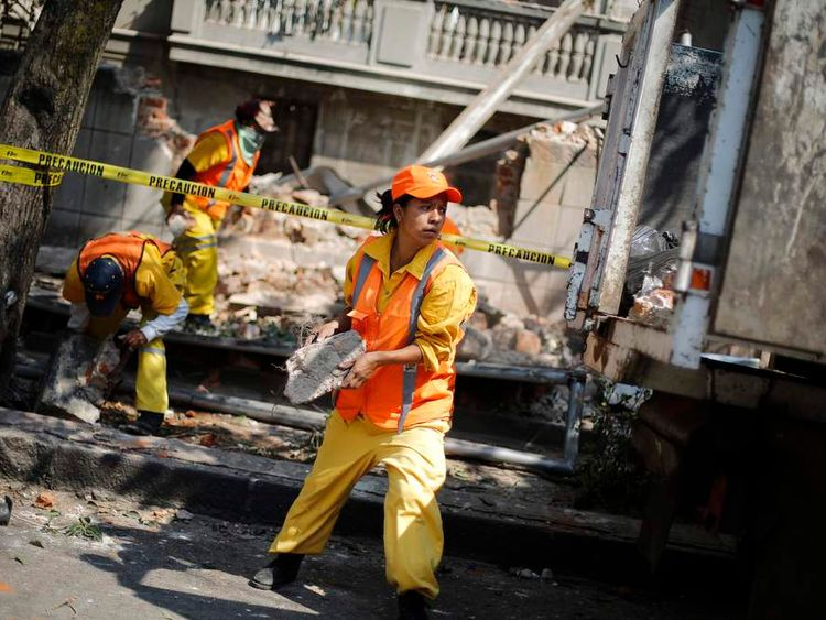 City workers remove the rubble of a wall that collapsed following an earthquake in Mexico City.