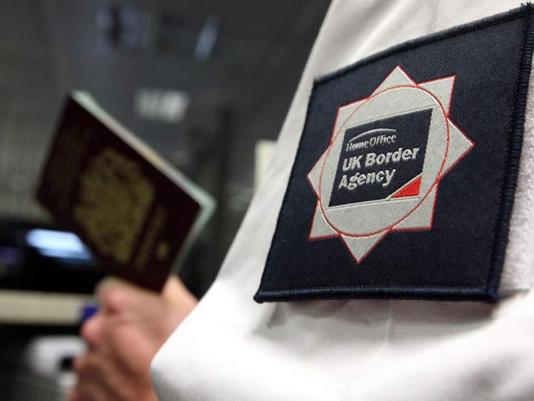 A UK Border Agency officer checking a passport