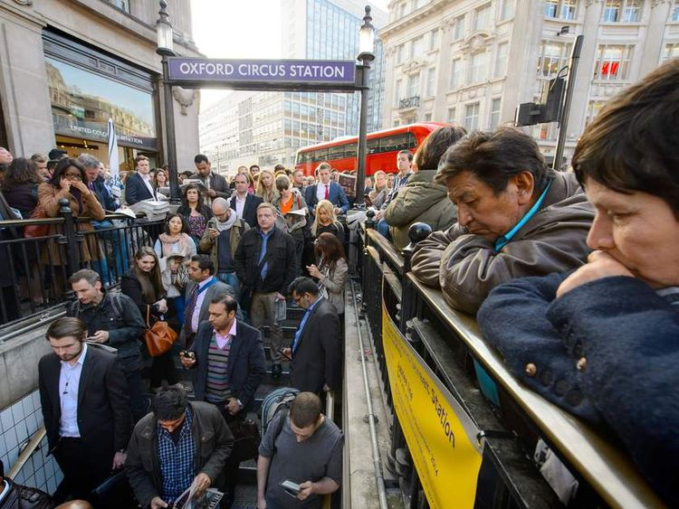 People queue outside Oxford Circus underground station, in central London, during the evening rush hour.