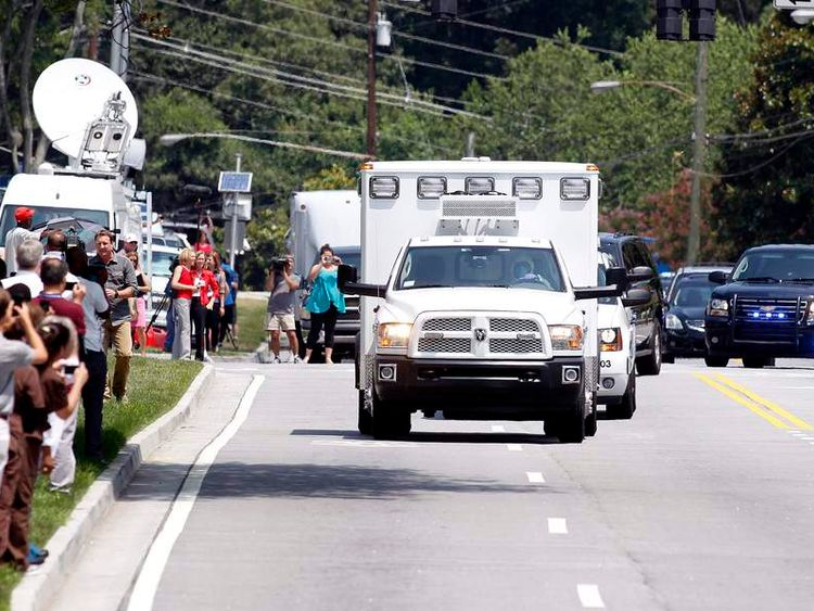 An ambulance carrying Nancy Wrtebol passes crowds in Atlanta