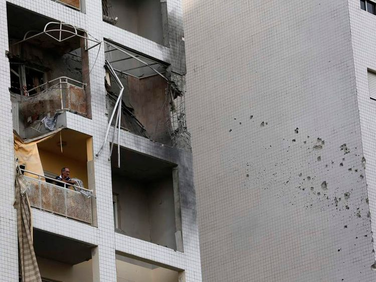 An Israeli man stands at the balcony of a damaged apartment building after a rocket fired by Palestinian militants in Gaza landed in the southern city of Ashdod