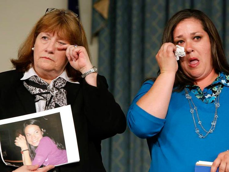 Family members of General Motors crash victims wipe away tears at a news conference in Washington