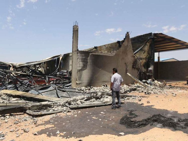 A man looks at destroyed warehouses following Friday's clashes between Libyan irregular forces and Islamist militias in Benghazi.