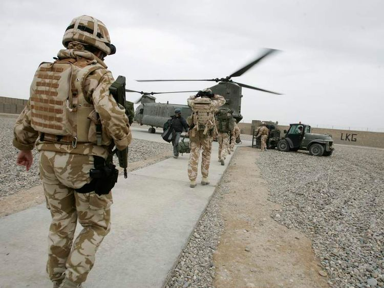 British soldiers walk to a Royal Air Force (RAF) Chinook helicopter for transport in Lashkar