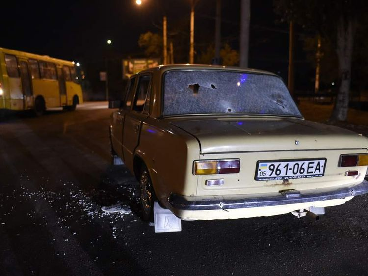 A car with bullet holes is parked on a street on the outskirts of Mariupol
