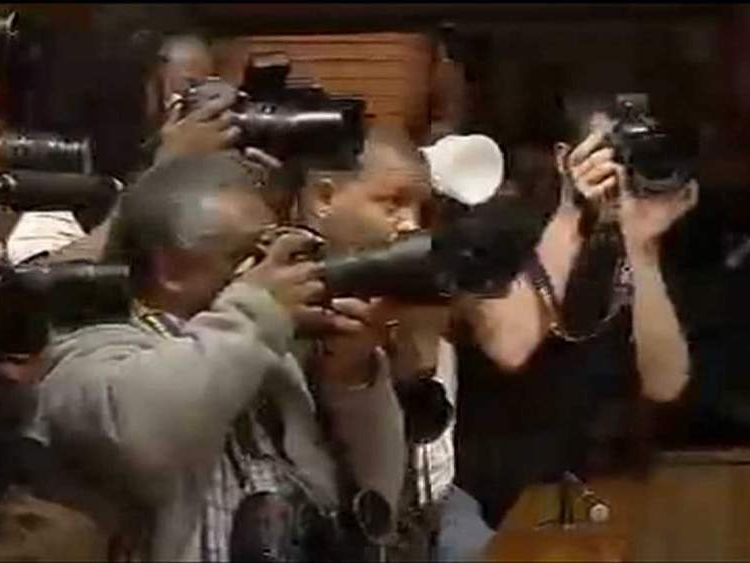 Photographers scramble for a picture of paralympian Oscar Pistorius as he returns to court