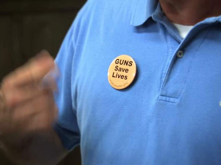 A man wears a badge reading 'Guns Save Lives'