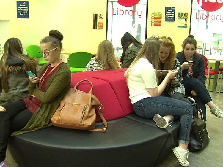 Blackburn college students using their phones during a break in lessons
