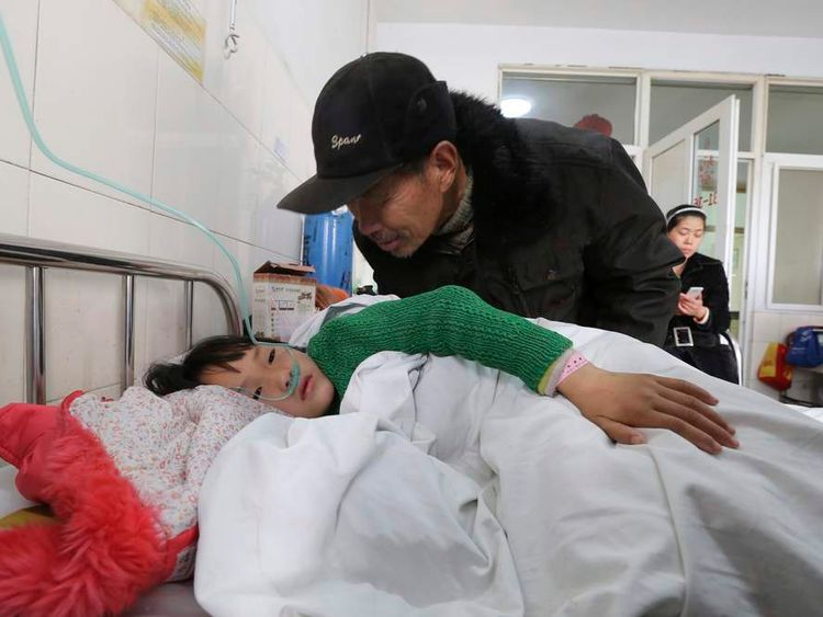 A man talks to a girl who was injured after a stampede accident at a primary school, at a hospital in Xiangyang, Hubei province