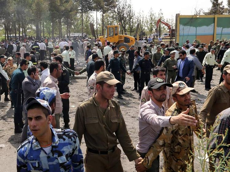 Iranian security forces secure the scene of a plane crash