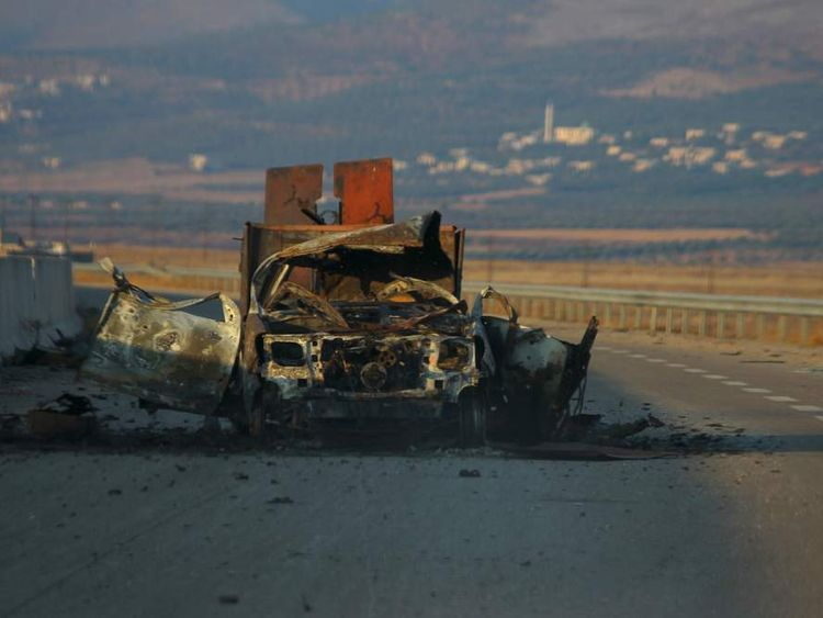 A damaged military vehicle is seen along a road in Idlib