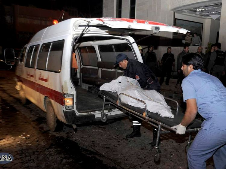 SANA photo shows a paramedic and a policeman loading a body into an ambulance after explosions at the main gate of the Syrian Interior Ministry in Damascus