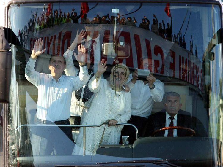 Tayyip Erdogan (L) and his wife Emine wave to supporters