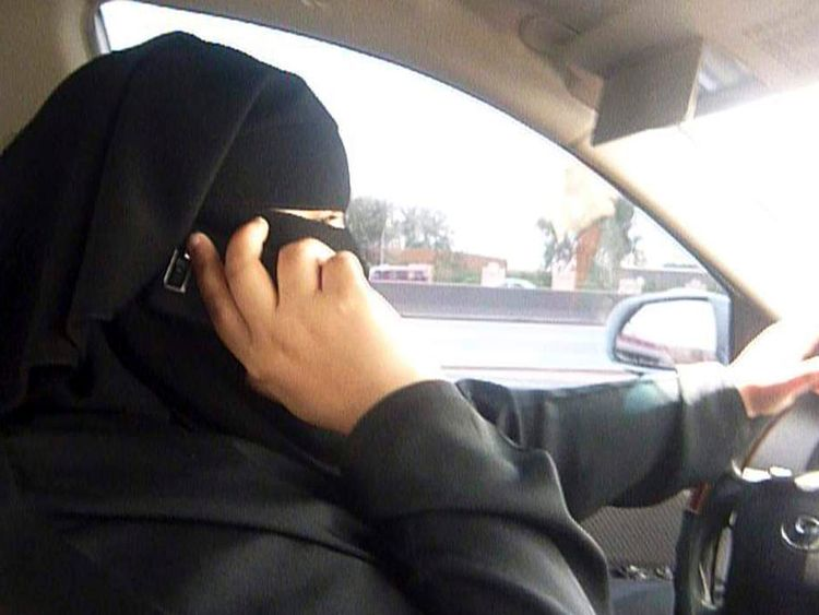 A woman sits behind the wheel of her vehicle