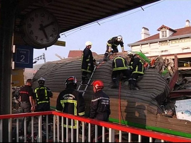 Fire crews at the scene of a train crash at Bretigny-sur-Orge station, outside Paris