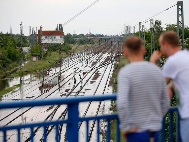 People look at flooded railway tracks near the river Elbe in Schoenebeck
