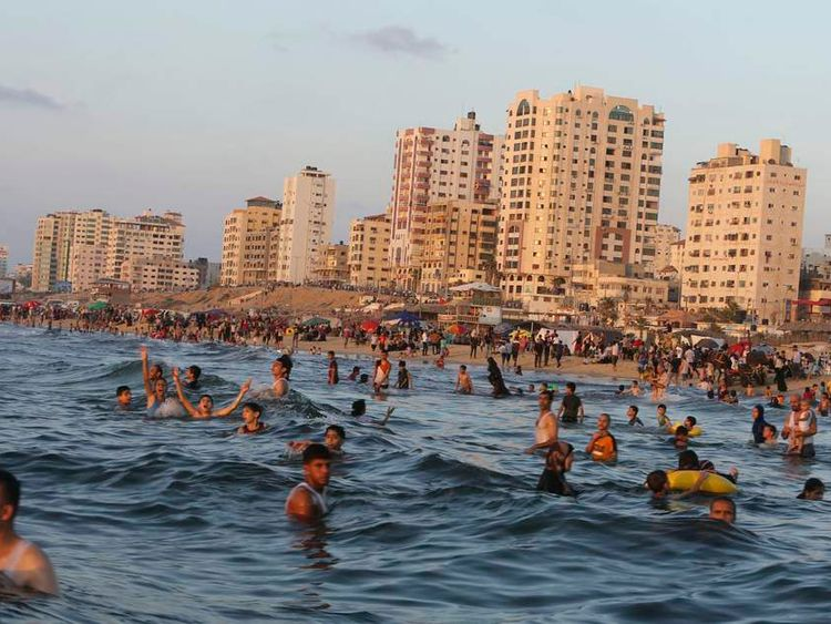 Palestinians swim in the Mediterranean Sea off the coast of Gaza City