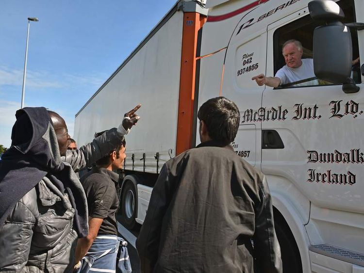 Migrants attempt to board a lorry heading into the UK.