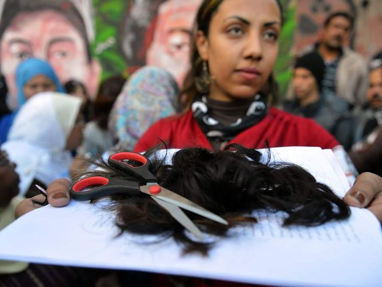 Egyptian Fatma al-Sharif,21, holds a bunch of hair cut from female protesters