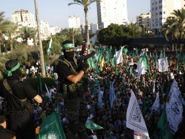 Palestinian militants from Hamas' armed wing rally