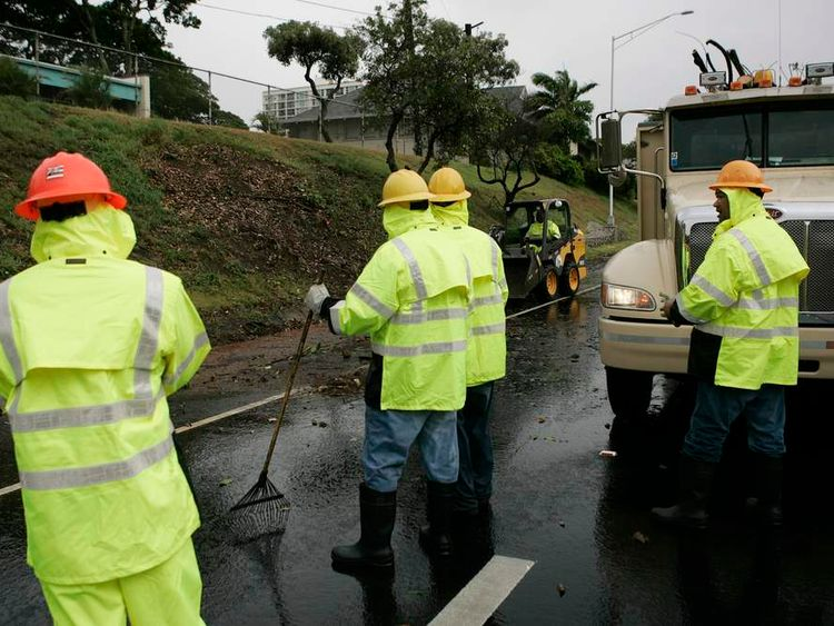 A road crew clears off debris from a downed tree in Honolulu, Hawaii