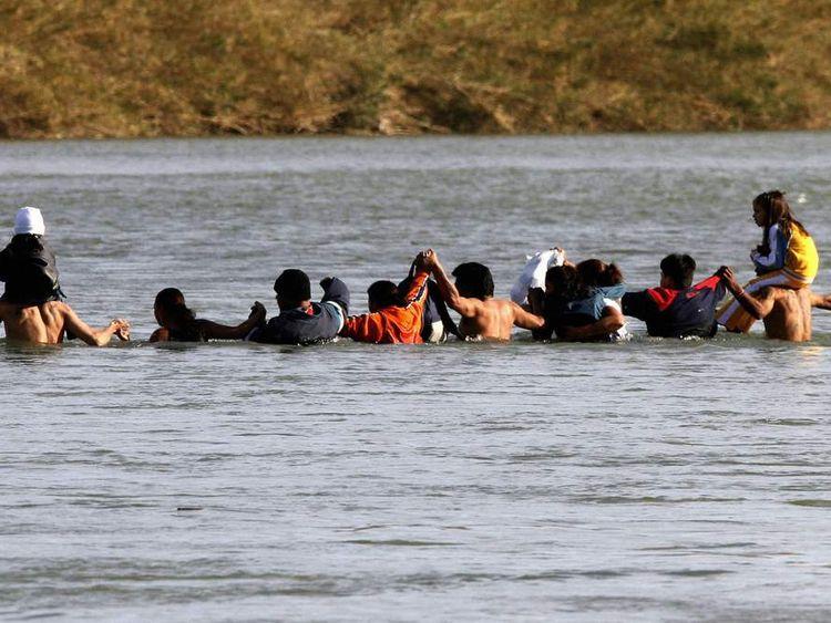 Immigrants, including children, illegally cross the Rio Bravo into the US