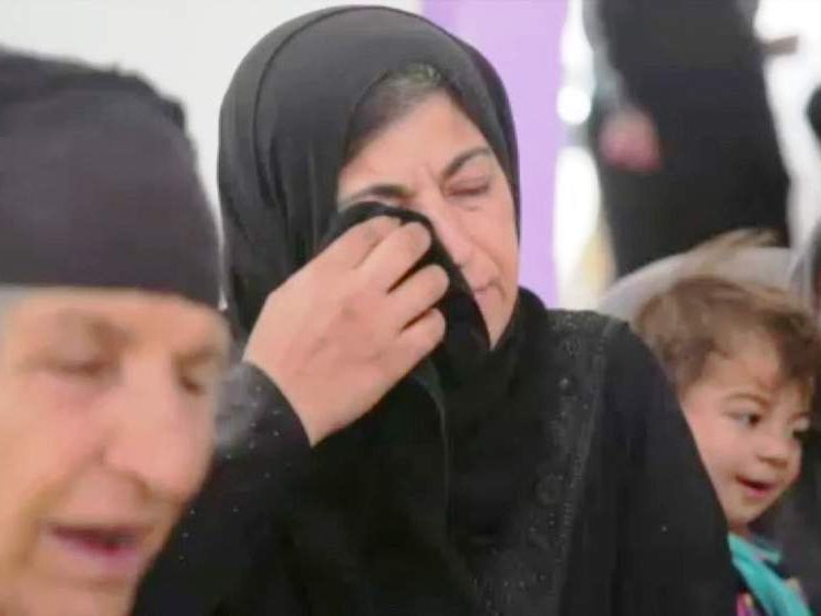 A woman rubs her eyes