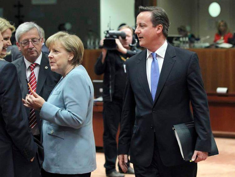David Cameron walks past Jose Manuel Barroso, Helle Thorning-Schmidt, Jean-Claude Juncker and Angela Merkel