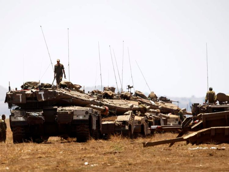 Israeli soldiers stand atop tanks before a drill near Kibbutz Ein Zivan close to the border crossing between Israel and Syria, in the Israeli-occupied Golan Heights