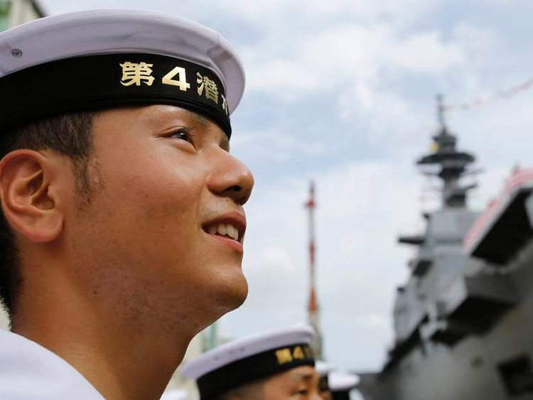 A member of Japan's Maritime Self-Defense Force looks at its new helicopter destroyer DDH183 Izumo before its launching ceremony in Yokohama